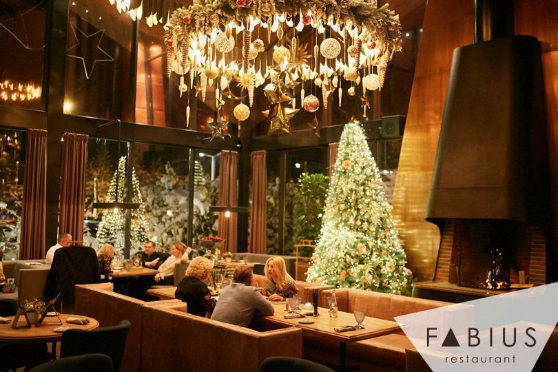 Christmas tree and decorations in restaurant with people