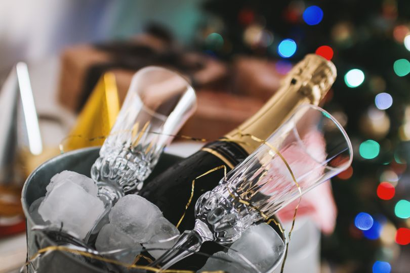 bottle of champagne with two glasses in bucket with ice