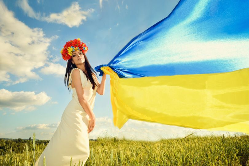 girl in field holding ukrainian flag