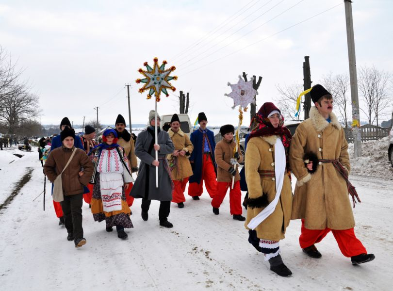 people in traditional ukrainian costumes with christmas symbols outdoor