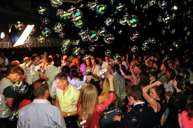 people dancing on a party with many soap bubbles