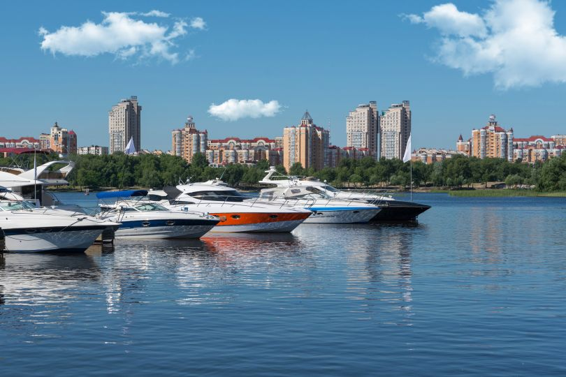 motor boats in river with city on background