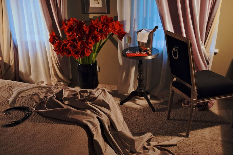 hotel room with classt furniture, glas of wine and vase with red flowers