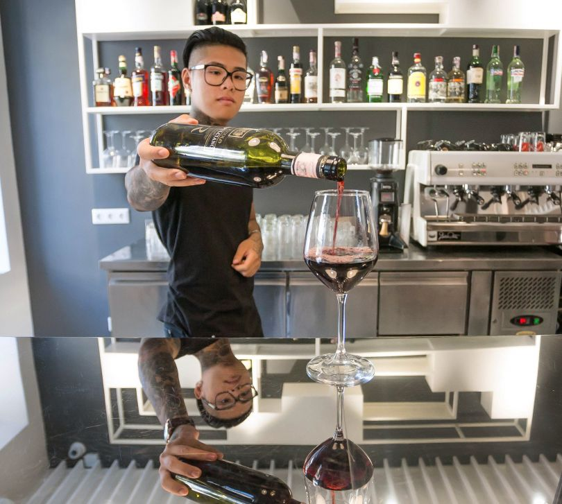 bartender puring wine into glass on bar counter