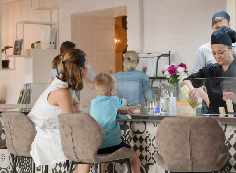 mother and son sitting at restaurant table while chef is working