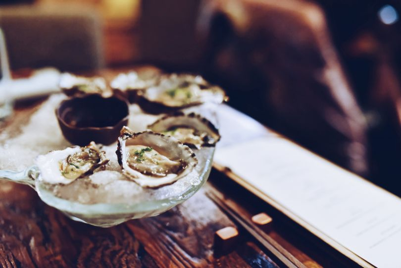 oysters in ice on glass plate on wooden table