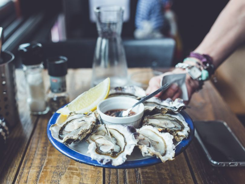 male hand holding plate of oysters served with lemon and sauce above wooden table with glass, phone, pepper and salt