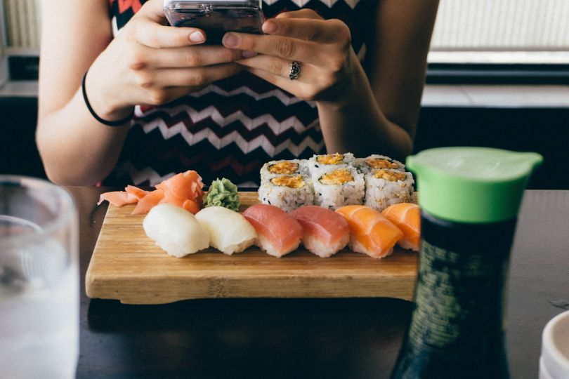Girl taking a pic of sushi
